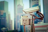 Vintage retro hipster style travel image of CCTV surveillance camera in Singapore with skyscapers in