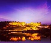 Vintage retro hipster style travel image of Amer Fort (Amber Fort) illuminated at night - one of pri