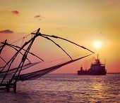Vintage retro hipster style travel image of Kochi chinese fishnets on sunset and modern ship. Fort Kochin, Kochi, Kerala, India