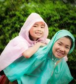 Asian Little Girl Enjoying The Rain Dressed In A Raincoat