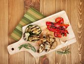 Grilled vegetables on cutting board over wooden table background. View from above