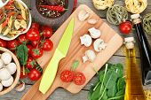 Fresh ingredients for cooking: pasta, tomato, mushroom and spices over wooden table background