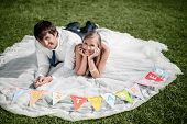Smiling Wedding Couple Lying On The Grass With