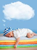 Yawning sleeping baby in funny hat with dream cloud for image or text