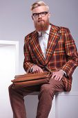 picture of long beard  - seated fashion man with long beard and briefcase looking at the camera - JPG