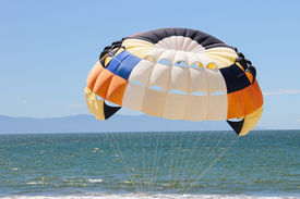 pic of parasailing  - Brilliant colors of a parasail above a Mexican beach - JPG