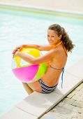 stock photo of pool ball  - Portrait of smiling young woman with ball sitting near swimming pool - JPG
