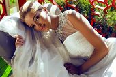 Beautiful Bride With Blond Hair In Wedding Dress Lying On Sofa