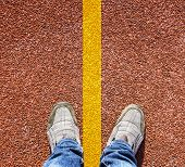 A Pair Of Feet Standing On A Running Track Rubber With A Yellow Stripe.
