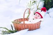 Funny happy baby boy wearing a warm snow suit and a red knitted snowman hat laying in a basket