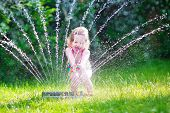 pic of sprinkler  - Funny laughing little girl in a colorful swimming suit running though garden sprinkler playing with water splashes having fun in the backyard on a sunny hot summer vacation day - JPG