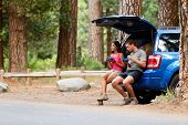 Couple on car road trip travel in eating in forest having lunch break outdoors smiling happy. Multiracial couple, Asian woman, Caucasian man People in Yosemite National Park, California, United States