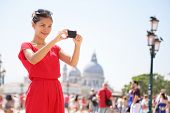 Asian woman taking picture photo with smartphone in Venice, Italy. Tourist girl using smart phone camera to take photograph on travel in Europe.