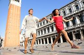 Travel couple in love having playful fun in Venice holding hands running laughing in Venice, Italy o