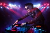 Handsome teenager dj mixing records in front of a crowd on stage