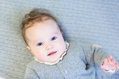 Sweet Baby Girl In A Warm Knitted Sweater On A Cable Knit Blanket