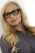 Beautiful blonde woman in black framed characterisctic glasses, looking away.