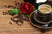 Cup Of Black Coffee And Red Rose Flower On Wooden Background
