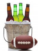 Closeup of an old fashioned beer bucket with three green bottles of cold beer and an American Football. Isolated on white with reflection.