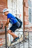 Child boy climbing over metal fence in a street, side view
