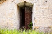 Open Rusted Door In Old Fortification Wall, Background Texture