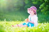 Toddler Girl Eating An Aple In The Garden
