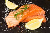 image of salmon steak  - two raw salmon steaks  on black board with spices and lemons - JPG