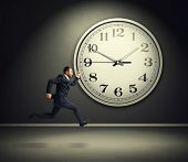 stock photo of running-late  - smiley running businessman and big white clock in dark room - JPG