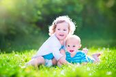 image of brother sister  - Cute little baby boy and a happy laughing toddler girl brother and sister playing together on a green lawn in the garden having fun on a sunny summer day - JPG