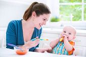 picture of child feeding  - Young attractive mother feeding her cute baby son giving him his first solid food healthy vegetable pure from carrot with a plastic spoon sitting in a white sunny kitchen at a window at home - JPG