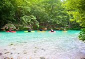 Happy group traveling by kayak on the green waters of Acheron river in Greece.