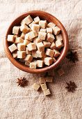 Brown sugar cubes and crystal sugar, spices in bowl on sackcloth background