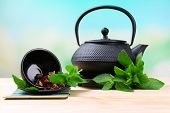 Chinese traditional teapot with fresh mint leaves and dried hibiscus petals on wooden table, on brig