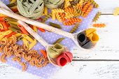 Colorful pasta in wooden spoons on wooden background