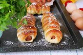 Baked sausage rolls in pan on table close-up