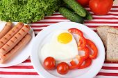 Scrambled eggs with sausage and vegetables served on plate on fabric background