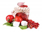 Sun dried tomatoes in glass jar, feta cheese and basil leaves isolated on white