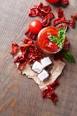 Sun dried tomatoes in glass jar, basil leaves and feta cheese on color wooden background