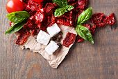 Sun dried and fresh tomatoes, basil leaves and feta cheese on color wooden background