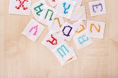Handmade embroidered letters on white fabric, on wooden background