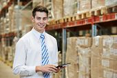 smiling manager in warehouse with tablet pc computer