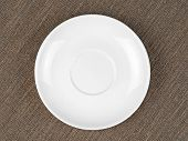 Single Empty White Plate On Coarse Fabric
