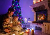 Two Little Sibling Boys And Their Dad Sitting By A Fireplace On Christmas Time.