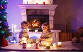 Two Little Children Sitting By A Fireplace At Home On Christmas Time.