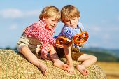 Two Little Sibling Boys And Friends Sitting On Hay Stack  And Eating Pretzel