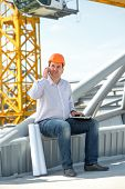 A Foreman With Drawings Speaking Phone At The Construction.