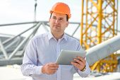 A Foreman With Digital Tablet At The Construction Supervising The Project.