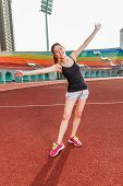 Chinese Woman Stretching On Track At Stadium