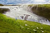 On a mountain slope the woman delighted looks at a boiling chasm. Powerful Gullfoss in Iceland.