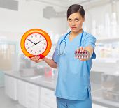 Young doctor with clock and pills at lab